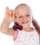 Little girl holding cherries Royalty Free Stock Photos