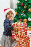 Little Girl Holding a Christmas Gift Stock Photos