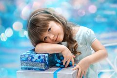 Little girl holding christmas gift. A little girl holding christmas gift on the blue background Stock Images