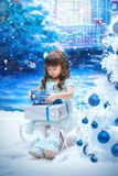 A little girl holding christmas gift. On the blue background Stock Photo