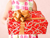 Little girl holding christmas gift box in the foreground Royalty Free Stock Photography