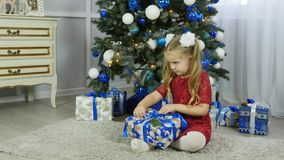 A little girl in a blue dress unpacks a New Year`s gift under a Christmas tree stock footage
