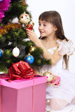 Little girl holding Christmas-tree decoration. Little smiling girl holding Christmas-tree decoration under a Christmas tree Stock Photography