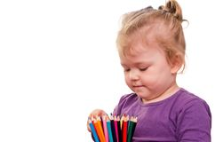 Little girl holding colored pencils in hands, isolated on white background royalty free stock images