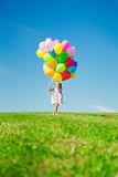 Little girl holding colorful balloons. Child playing on a green Royalty Free Stock Image
