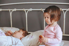 Little girl holding cookie sitting over the bed Stock Photo