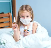 Little girl  holding a cough syrup bottle. Dissatisfied little girl with influenza in bed, holding a cough syrup bottle Royalty Free Stock Photos