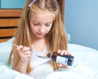 Little girl  holding a cough syrup bottle. Little girl with influenza in bed, holding a cough syrup bottle Stock Image