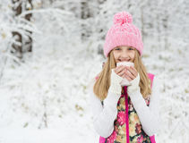 Little girl holding a cup of hot drink and smiling Royalty Free Stock Photos