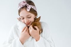 Little girl holding cute furry rabbits isolated on white Royalty Free Stock Images