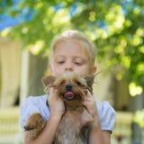 Little girl holding a dog stock photos