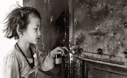 Little girl holding the door of closed classroom waiting for teacher to open, Sapa, Vietnam royalty free stock photos