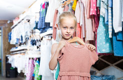 Little girl holding dress in hands in children clothes boutique Royalty Free Stock Photos