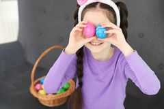 Little girl holding Easter eggs near eyes royalty free stock photo