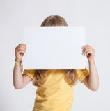 Little girl holding empty sheet of a paper Stock Images