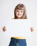Little girl holding empty sheet of a paper royalty free stock photography
