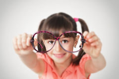Little girl holding eyeglasses, health eyesight concept.Soft fo Stock Images