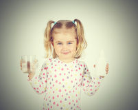 Little girl holding filter for drinking water and  glass of clea Stock Photos