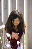 Little girl holding flower. A little girl holding a white flower in her hands as she looks into it Royalty Free Stock Photos