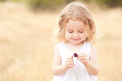 Little girl holding flower Stock Photos