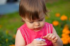 Little girl  holding flower outdoors Stock Photo
