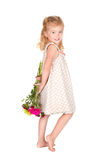 Little girl holding flowers behind her back Royalty Free Stock Photography
