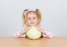 Little girl holding forks of cabbage. Stock Images
