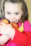 Little girl holding fruit royalty free stock photography