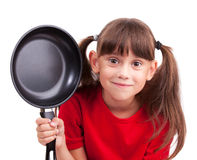 Little girl holding a frying pan Stock Images