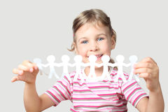 Little girl holding garland of paper little people Royalty Free Stock Image