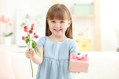 Little girl holding gift box and flower for Mother`s day Royalty Free Stock Image