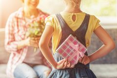 Little Girl Holding Gift Box for Her Beautiful Mom stock images