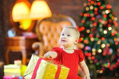 Girl holding a gift by a red ribbon, against the background of a festive Christmas tree stock images