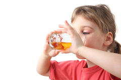 Little girl holding glass with juice for two hands Stock Photo