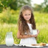 Little girl holding glass of milk outdoor summer. Little girl holding glass of milk outdoor. Curly kid having breakfast. Summer time Stock Photos