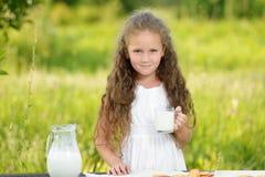 Little girl holding glass of milk outdoor summer. Little girl holding glass of milk outdoor. Curly kid having breakfast. Summer time Stock Photography