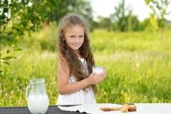 Little girl holding glass of milk outdoor summer. Little girl holding glass of milk outdoor. Curly kid having breakfast. Summer time Royalty Free Stock Photo