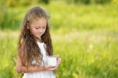 Little girl holding glass of milk outdoor summer. Little girl holding glass of milk outdoor. Curly kid having breakfast. Summer time Stock Image