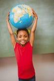 Little girl holding globe over head Stock Photo