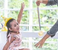 Little girl holding gold medal for student award. Little girl is holding gold medal for student award royalty free stock photo