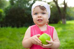 Little girl holding green apple Royalty Free Stock Photos