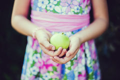 Little girl holding green apple in her hands Royalty Free Stock Photos