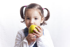 Little girl holding a green apple. Portrait of happy girl biting a green apple. Isolated over white background royalty free stock photos