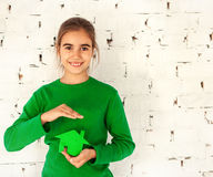 Little girl holding green house in hands Stock Photo