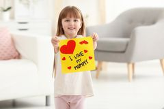 Little girl holding greeting card for Mother`s day Stock Photos