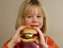 Little girl holding hamburger. Stock Image