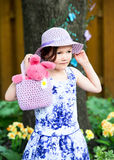 Little Girl Holding a Hand Bag with an Easter Bunny Stock Photos