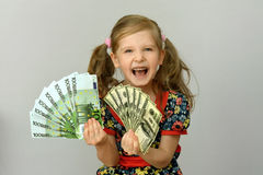 Little girl holding in hands a pack of dollars and Euro Royalty Free Stock Photos
