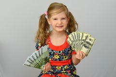 Little girl holding in hands a pack of dollars and Euro. Little girl holding in hands a pack of dollars and Euro Stock Photography