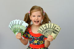 Little girl holding in hands a pack of dollars and Euro. Little girl holding in hands a pack of dollars and Euro Royalty Free Stock Photos